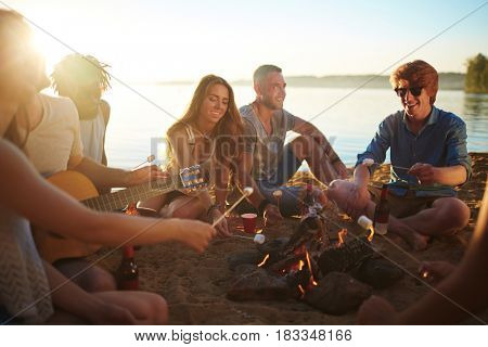 Happy guys and girls spending weekend on the beach