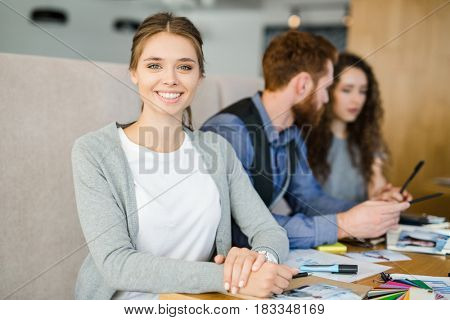 Pretty young specialist looking at camera by workplace in working environment