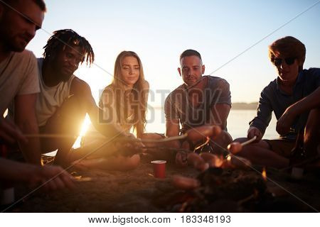 Multi-ethnic friends making snack on campfire while relaxing by water