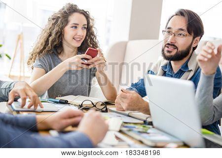 Young businesswoman with smartphone listening to her colleagues conversation at meeting
