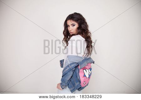 a girl in a white suit and denim jacket posing