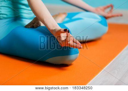 Young sportswoman in padmasana pose on rug