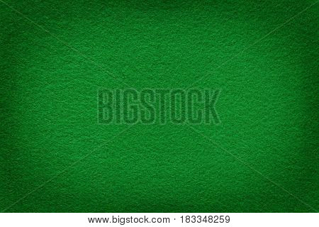 Green felt surface with light copy space in center. Texture and background