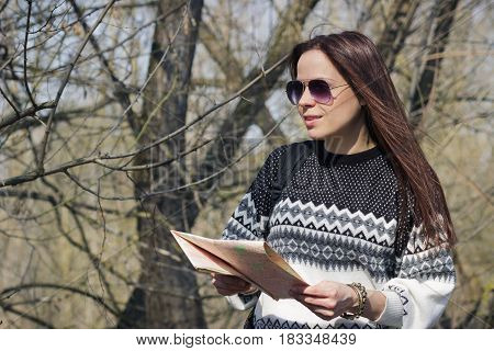 Woman Walks In The Spring's Forest With A Map In The Hand