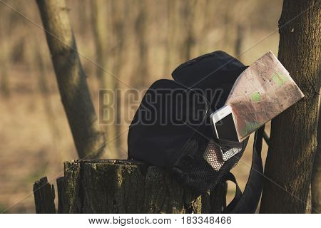 Backpack With Phone And Map In The Pocket On The Stump