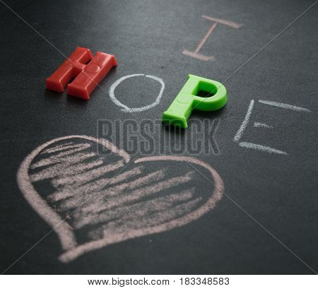 The inscription I hope with chalk and plastic letters on a dark background and a heart
