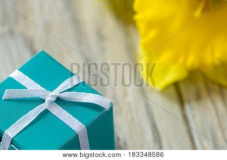 Present-box and blurred yellow flower on background, close-up