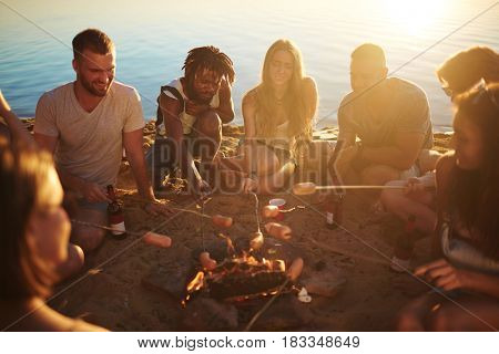 Young buddies roasting sausages on campfire while sitting on sand by water