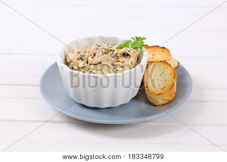 bowl of grated cheese spread with olives and croutons on grey plate