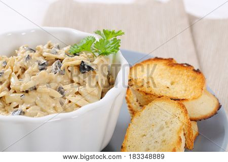 bowl of grated cheese spread with olives and croutons on grey plate - close up