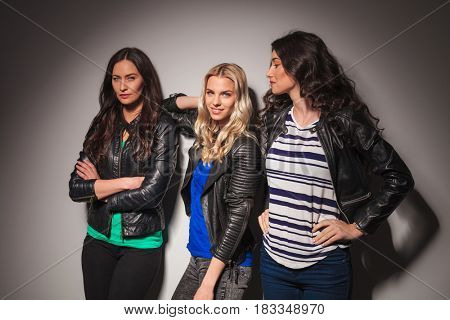 three young casual women in leather jackets posing in studio