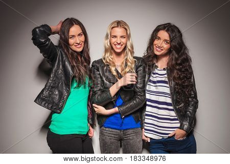 three young casual women having fun together against gray studio wall