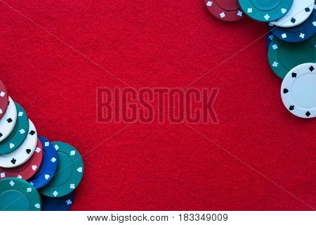 Red felt table with poker chips over it and copy space. Casino gambling poker and roulette theme background
