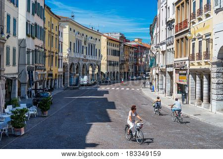 Udine - August of 2013, Friuli Venezia Giulia region, Italy: Street of Udine, people are cycling on the main street of the old city center in sunny summer day