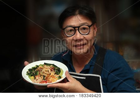 Thai Chinese food Chef holding a plate of fried big noodle with marinated chicken in soy sauce and vegetable call Sen Yai Pad Cee Oue in Thai.