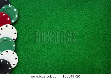 Poker chips on green felt casino table. Gambling poker blackjack and roulette theme background