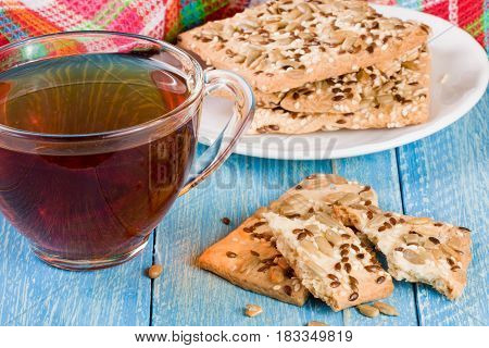 crispy bread with seeds of sunflower, flax and sesame seeds with a cup of tea on a blue wooden background.
