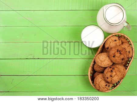 jug and glass of milk with oatmeal cookies in a wicker basket on a green wooden background with copy space for your text. Top view.