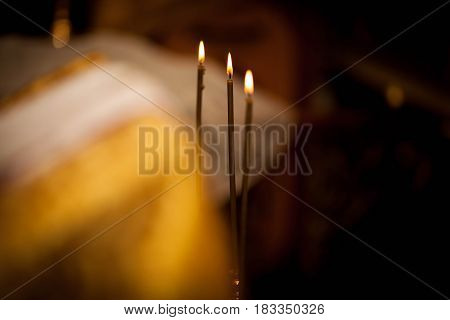 three church candles on a black background
