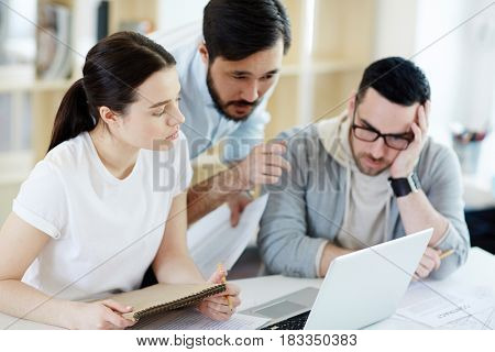 Group of business people working with laptop in modern office: Asian man leaning to help troubled colleagues with problem