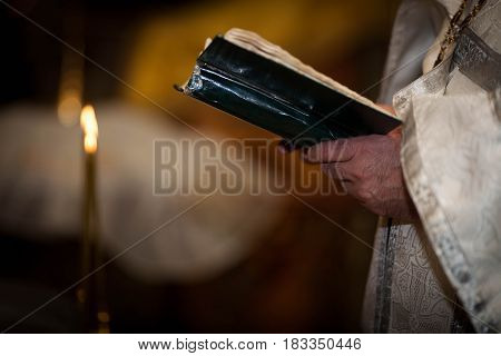 the priest holds the Bible on black background