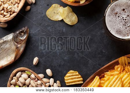 Lager beer and snacks on stone table. Nuts, chips, dry fish. Top view with copy space