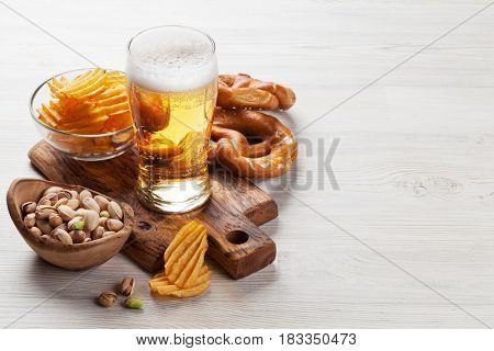 Lager beer and snacks on wooden table. Nuts, chips, pretzel. With copy space