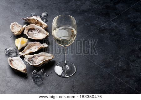Opened oysters, ice and lemon with white wine over stone table. Half dozen. With copy space