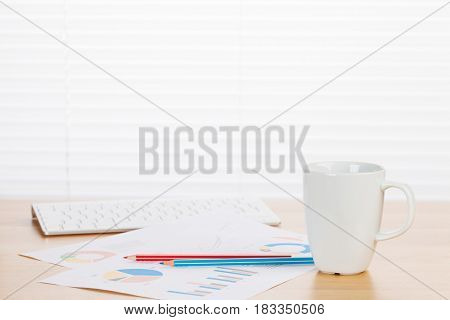 Office workplace with supplies and reports on wood desk table in front of window with blinds