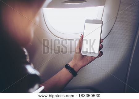 Mockup image of a woman holding and looking at smart phone with blank white screen next to an airplane window with clouds and sky background