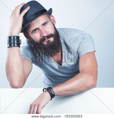 Portrait of young man in hat standing near blank, isolated on white background.