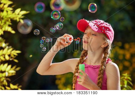 natural light blowing bubbles girl
