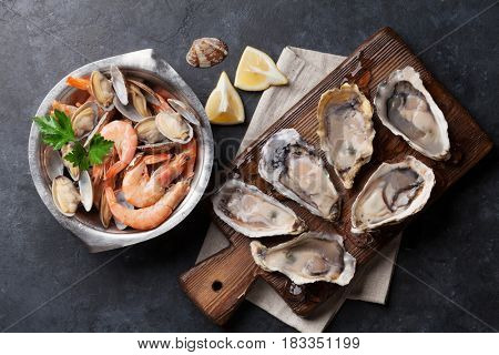 Fresh seafood on stone table. Scallops, oysters and shrimps. Top view