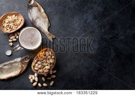 Lager beer and snacks on stone table. Nuts, salted fish. Top view with copy space