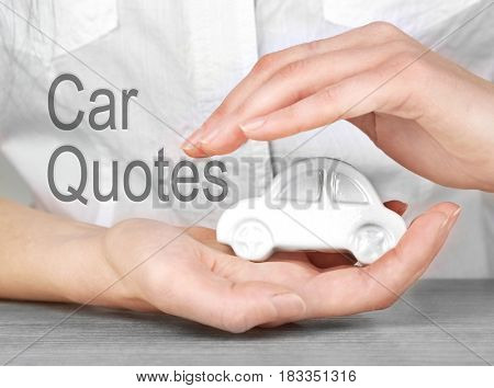 Car quotes concept. Female hands and toy automobile