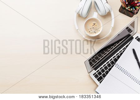Office desk workplace with laptop, coffee and headphones on wooden background. Top view with copy space
