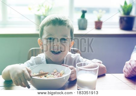 Little Boy Enjoying Bowl Of Cereal