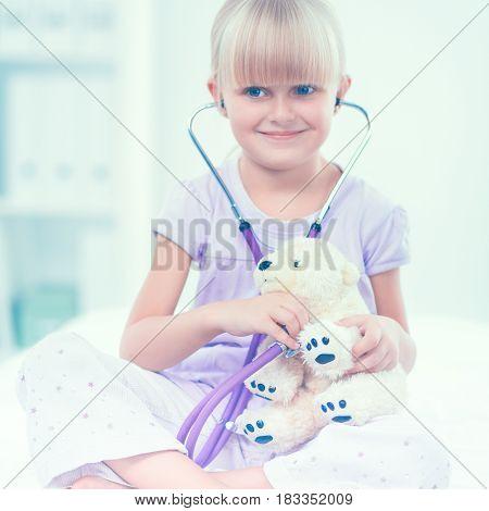 Little girl is examining her teddy bear using stethoscope.