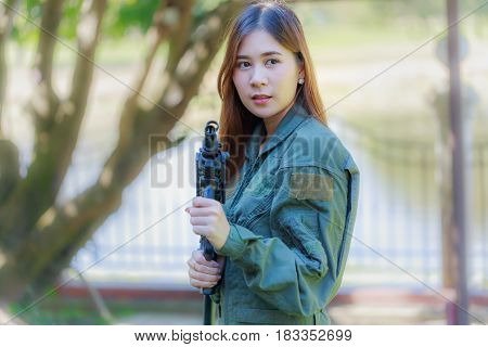 Young pretty Asian woman in military pilot outfit holding a rifle M-16 blur background.