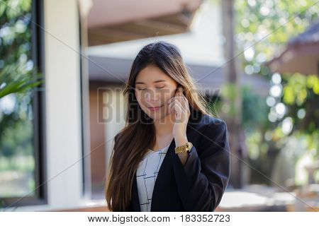 Pretty young Asian woman using smart mobile phone cellphone. She's working in the comfort surrounding atmosphere feeling happy and relaxing.