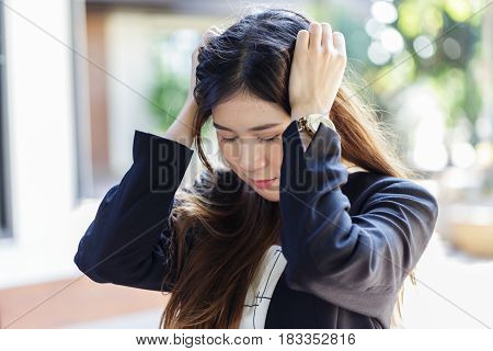 Pretty Asian young business woman with headache, holding both of her hands to her head. Trying hard to focusing on her work, feeling stressful and exhausting.