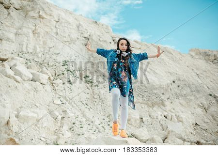 Young woman with headphones posing and dancing near the beautiful mountains wearing colorful clothes