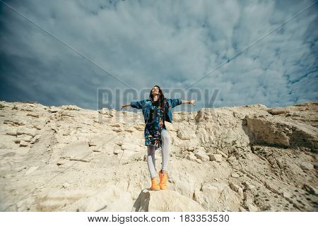 Young woman posing and dancing near the beautiful mountains dressed colorful clothes