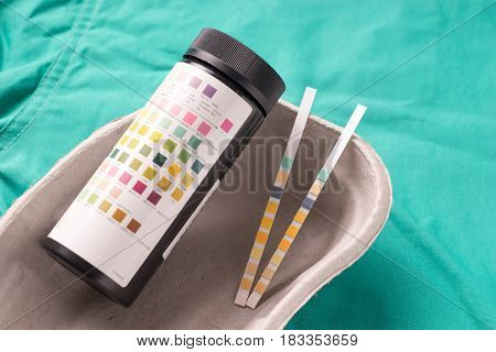 Medical Urine test striis lying in a one use capsule on the hospital's green background. The background can be a textile part of a doctor or nurse's work uniform