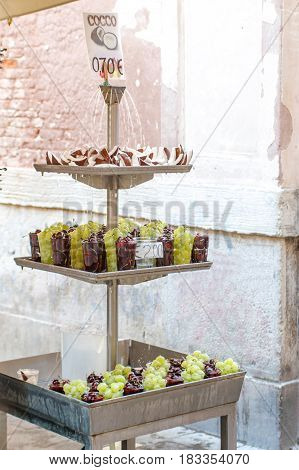 A portrait view of fountain with water drops falling on coconut slices and variety fresh red cherries and green grapes in a cups at local market for sale in Venice, Italy