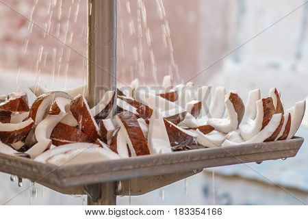 A close-up view of water drops falling on coconut slices at local market for sale in Venice, Italy. Selected focus