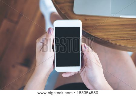 Mockup image of hands holding white mobile phone with blank black screen on thigh with silver color laptop on table and wooden floor background