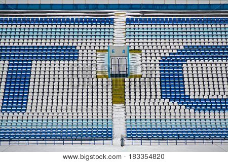 Background of white and blue stadium seats with exit in centre