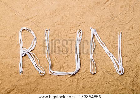 Run sign made of white shoelaces against sand background, studio shot, flat lay.