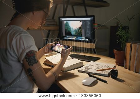 Photo of young woman designer sitting indoors at night play games by mobile phone.
